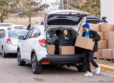 A food shelf employee loads boxes of food into the back of a car