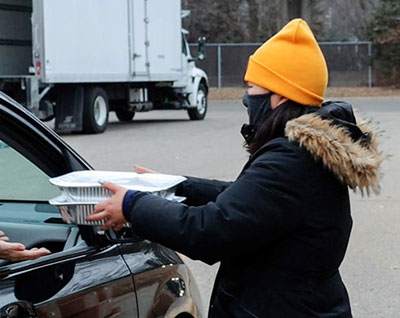 A Minnesota Central Kitchen employee delivers two prepared meals into a car in the drive up line